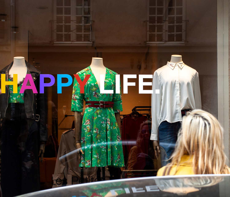 saldi-estivi,-vetrina-con-scritta-happy-life,-COMINshop