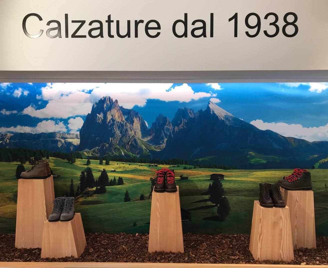 tendenze arredamento negozi, scarponi da montagna appoggiati su piedistalli in legno con paesaggio Dolomitico sullo sfondo, realizzazione COMINshop